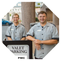 Two valet smiling at camera by a PMC booth